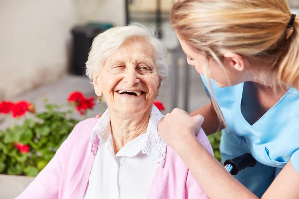 Lachende vrouw met inwonende verpleegster aan huis