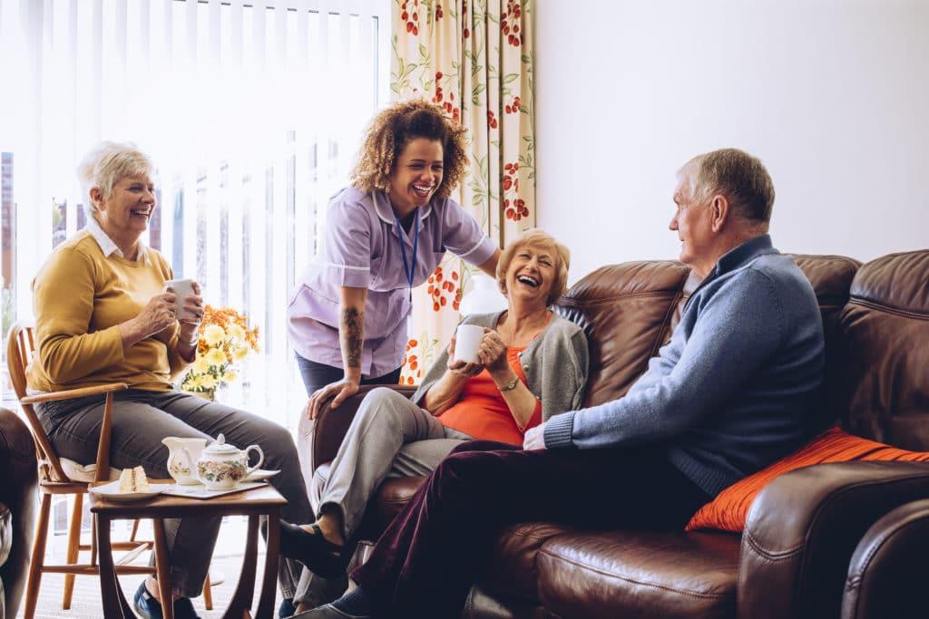 Ouderen genieten van een kop koffie in hun huis, met zorg van een verpleger aan huis