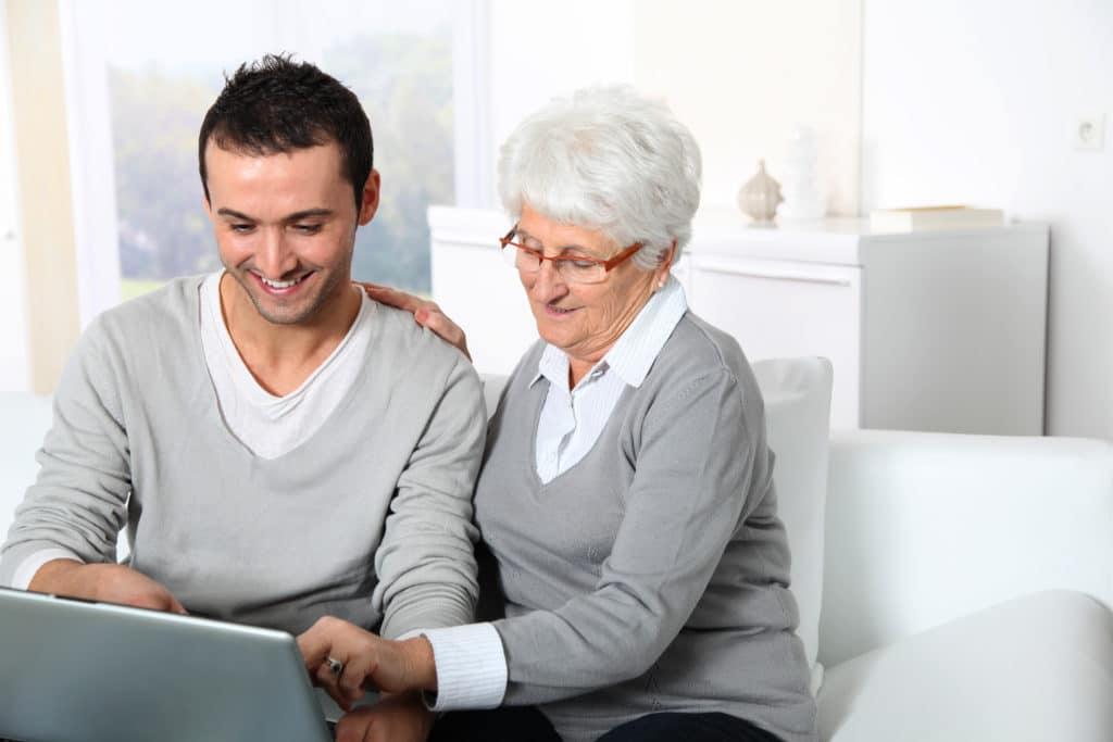 Jonge mannelijke zorgverlener helpt oudere vrouw met internet